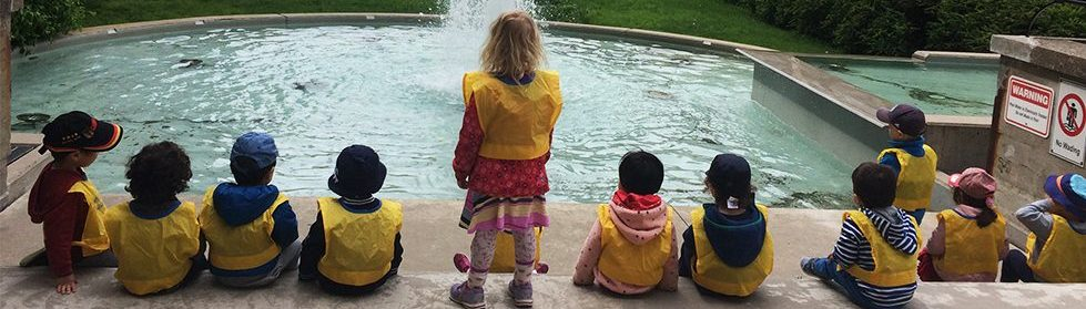 Children sitting in front of a fountain